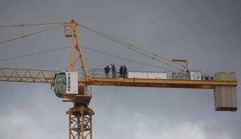 Workers protesting labor conditions on a crane at a Ra'anana construction site on March 2, 2015.