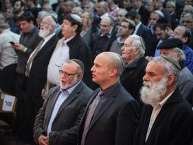 Party leader Naftali Bennett, (front row, center) and Rabbi Avichai Rontzki (front row, right) at a meeting of Habayit Hayehudi before the 2015 election.
