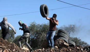 Palestinian protesters hurl tires at IDF troops during a demonstration in the village of Kfar Qaddum, near Nablus, on Friday.