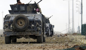 Iraqi counter-terrorism forces stand guard on a road south of the Anbar province's capital Ramadi on December 24, 2015.