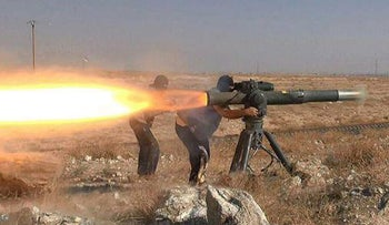 In this image posted online June 26, 2015 by supporters of the Islamic State militant group on an anonymous photo sharing website, Islamic State militants fire an anti-tank missile in Hassakeh, northeast Syria.