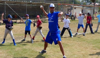 Nate Fish, director of the Israel Association of Baseball, demonstrating pitching to Israeli kids. (Margo Sugarman/IAB)