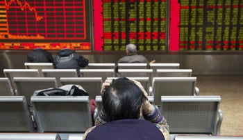 An investor sits in front of an electronic board showing stock information at a brokerage house.