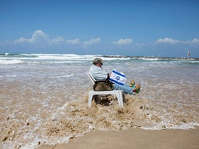 A man with an Israeli flag sits on a chair in the sea on Independence Day, April 23, 2015.