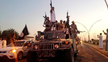 Islamic State fighters parade in a commandeered Iraqi army vehicle down a main road in Mosul, Iraq, June 23, 2014.