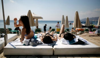 Tourists sunbathe on the beach in the Red Sea resort city of Eilat