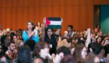 A woman holds up a Palestinian flag at the 2014 NWSA Conference.
