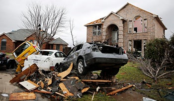 Cars are piled on top of each other on December 28, 2015, in Garland, Texas. Residents surveyed the destruction from deadly tornadoes in North Texas as the same storm system brought winter woes to the Midwest on Monday, amplifying flooding that's blamed for more than a dozen deaths and prompting hundreds of flight cancellations.