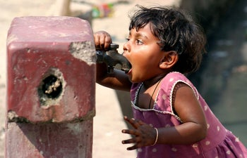An girl drinks water from a roadside tap in the northeastern Indian city of Siliguri.