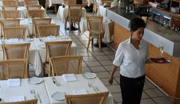 A waitress walks past empty tables at the Mul Yam restaurant in Tel Aviv Port.