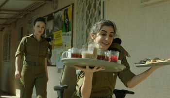 An illustrative image from the film 'Zero Motivation' shows a scene in which an Israeli soldier carryies a tray of coffee cups to an officers' meeting.