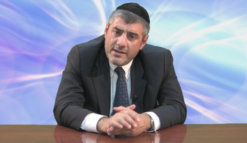 Rabbi Yosef Mizrachi sits at a desk.