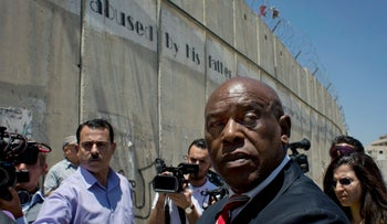 Tokyo Sexwale, foreground, FIFA's mediator or Israeli-Palestinian soccer dispute, in front of the separation barrier on the outskirts of the West Bank city of Ramallah, May 7, 2015.