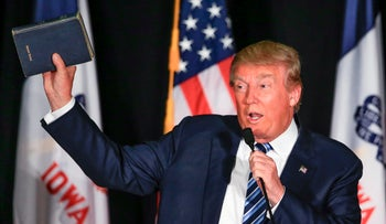 Republican presidential candidate Donald Trump holds up his Bible during a campaign stop in Iowa, December 29, 2015.