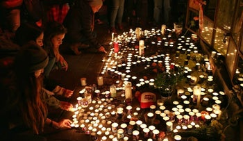 Mourners place candles at the scene of a deadly shooting attack in downtown Tel Aviv on January 2, 2016.