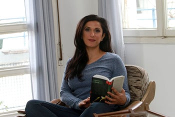 Israeli author Dorit Rabinyan poses with her Hebrew-language novel titled 'Gader Haya' (known in English as 'Borderlife') on December 31, 2015 at her home in Tel Aviv.