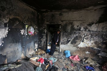 A relative stands on January 3, 2016, inside the burned-out home of Saad Dawabsha, who was killed alongside his toddler and his wife when their house was firebombed on July 31, 2015 in the West Bank village of Duma.