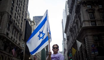 A boy walks with a flag during the Celebrate Israel Parade along Fifth Avenue May 31, 2015 in New York City.