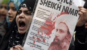 A protester holds a placard during a demonstration against the execution of Shi'ite cleric Sheikh Nimr al-Nimr in Saudi Arabia, outside the Saudi Arabian Embassy in London, Britain, January 3, 2016.