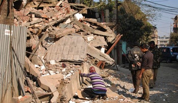 Indian men inspect the damage caused to a building that collapsed in an earthquake in Imphal, capital of the northeastern Indian state of Manipur, Monday, Jan. 4, 2016.