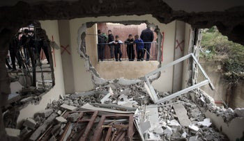 Palestinian boys look into the house of Bahaa Elayan, after it was demolished by Israeli forces, in the East Jerusalem neighborhood of Jabal Mukaber, January 4, 2016.