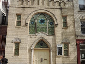 Harlem's Old Broadway Synagogue. The sole surviving synagogue in New York City's Harlem neighborhood today is light-colored brick, with stained glass windows.