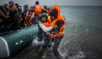 Refugees and migrants disembark on a beach after crossing a part of the Aegean sea from Turkey to the Greek island of Lesbos, January 3, 2016.