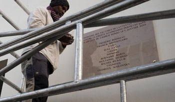 A worker stands beside the Charlie Hebdo plaque that will be unveiled on Tuesday. It includes the misspelled name of Georges Wolinski.