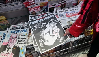 A woman looks at the special commemorative edition of French satirical newspaper Charlie Hebdo at a newsstand in Paris, on January 6, 2015.