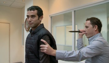 Channel 1 reporter Eitam Lachover, left, being stabbed in the back in a test of the protective jacket he was wearing, January 6, 2016.