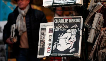 """The latest edition of French weekly newspaper Charlie Hebdo with the title """"One year on, the assassin still on the run"""" is displayed at a kiosk in Nice, France, January 6, 2016."""