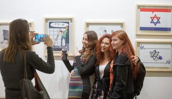 """Amit Katz (second from left), winner of the """"Cartoon*Criticism*Care"""" competition, poses with friends at the opening in Jerusalem of an exhibition of satirical drawings by Israeli high-school students marking the anniversary of the Charlie Hebdo attack."""