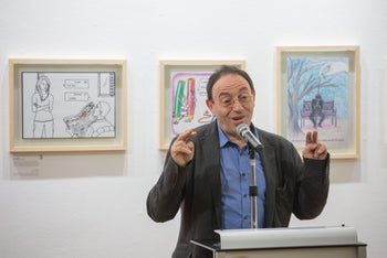 Israeli political cartoonist Michel Kichka speaks at the opening of an exhibition featuring the best works in a competition by Israeli high-school students marking the anniversary of the Charlie Hebdo attack.