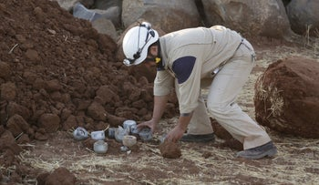 A man gathers unexploded cluster bomblets that activists say were fired by the Russian air force at Maasran, Syria, October 7, 2015.