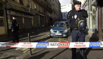 An officer stands behind a police cordon set up in Paris on January 7, 2016, after police shot a man dead as he was trying to enter a police station.
