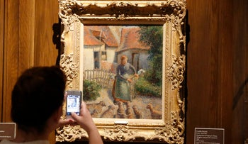 "Visitor to the Fred Jones Jr. Museum of Art at the University of Oklahoma photographing ""Shepherdess Bringing in Sheep"" by French impressionist artist Camille Pissarro. A federal judge has suspended activity in a lawsuit challenging the ownership of ""Shepherdess Bringing in Sheep"" as negotiations continue with a French woman who claims she is the rightful heir. (AP Photo/Sue Ogrocki, File)"