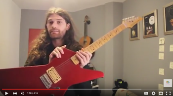 Screenshot from YouTube of Arnold Nesis holding the gifted guitar in his room.