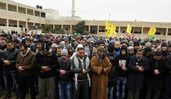 Palestinian mourners pray over the bodies of Anas Hamad and Mohammed Ayad, who were killed after reportedly perpetrating car-ramming attacks, during their funeral in Silwad, January 3, 2015.