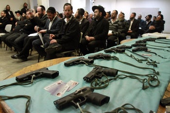 Ultra Orthodox residents of Betar examine guns for sale, Wednesday, January 6, 2016.
