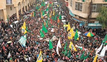 Hundreds of mourners walk down a Hebron street during the mass funeral of 14 Palestinians killed in recent attacks, January 2, 2016.