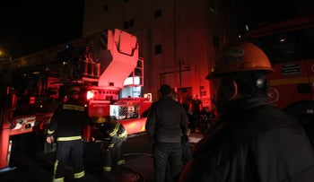 Firefighters at the scene of the fire in Jerusalem, outside the building that houses the office of the left-wing NGO B'Tselem, January 10, 2016.