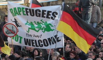 """Right-wing demonstrators hold a sign """"Rapefugees not welcome - !Stay away!"""" and a sign with a crossed out mosque as they march in Cologne, Germany, January 9, 2016."""