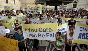 Hundreds of Israeli Christians hold banners in a rally against what they said was state discrimination in funding their schools at the foot of the Basilica of the Annunciation in Nazareth on September 1, 2015.