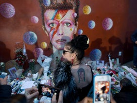 A woman with a tattoo on her back looks at a mural of British singer David Bowie by artist Jimmy C in Brixton, south London, Monday, Jan. 11, 2016.