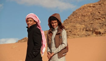 """Jacir Eid Al-Hwietat, right, and his cousin, Hussein Salameh al-Sweilhiyeen pose in a desert in southern Jordan, January 9, 2016. Both from a Bedouin clan, acted in the film """"Theeb""""."""