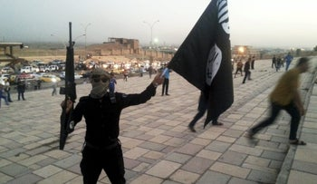 An Islamic State fighter holds an ISIS flag and a weapon on a street in the city of Mosul, Iraq, in a June 23, 2014.