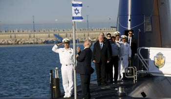 Prime Minister Benjamin Netanyahu raises the Israeli national flag during a ceremony taken on the Rahav, the fifth submarine in the fleet, after it arrived in Haifa port January 12, 2016.