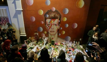 People gather next to tributes placed near a mural of British singer David Bowie by artist Jimmy C, in Brixton, south London, Monday, Jan. 11, 2016.
