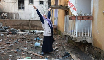 A woman cries in the compound of a destroyed police station in Cinar, in the mostly-Kurdish Diyarbakir province in southeastern Turkey on January 14, 2016.