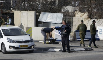 An Israeli policeman stands guard at the scene where a Palestinian, who the Israeli military said tried to stab an Israeli soldier, was killed by Israeli troops, near the West Bank city of Hebron January 14, 2016.